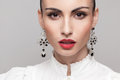 Headshot of fashionable model with perfect makeup and hairstyle red lips white shirt big earrings Royalty Free Stock Photo