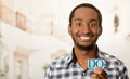 Headshot handsome man holding up small letters spelling the word do and smiling to camera Royalty Free Stock Photo