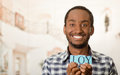 Headshot handsome man holding up small letters spelling the word joy and smiling to camera Royalty Free Stock Photo