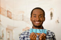 Headshot handsome man holding up small letters spelling the word time and smiling to camera Royalty Free Stock Photo