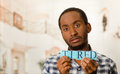 Headshot handsome man holding up small letters spelling the word tired and looking to camera Royalty Free Stock Photo