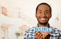 Headshot handsome man holding up small letters spelling the word work and smiling to camera Royalty Free Stock Photo