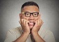 Headshot nerdy guy with glasses biting his nails looking anxious craving closeup portrait young at you for something or Stock Photography