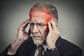 Headshot senior man suffering from headache hands on head closeup with red colored inflamed areas looking down isolated gray Stock Images