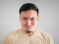 Headshot of smell something bad face of Asian man.