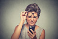 Headshot young woman with glasses having trouble seeing cell phone Royalty Free Stock Photo