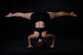 Headstand and splits female dancer performing isolated on a black background Royalty Free Stock Photography
