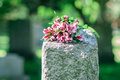 Headstone in cemetery with flowers for concept of death and loss Royalty Free Stock Images