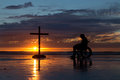 Healing cross man in a wheel chair by a at a beach as the sunset Stock Image