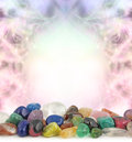 Healing crystals border decorative pastel colored frame background with a selection of multicolored tumbled at the front and Royalty Free Stock Photography