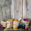 Healing herbs in hessian bags and  bottles with tincture on Royalty Free Stock Photo