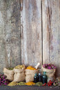 Healing herbs in hessian bags on old wooden background Royalty Free Stock Photo