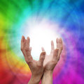 Healing vortex female hands reaching up with white light between on a swirling rainbow colored background Stock Image