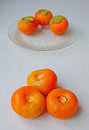 Health benefits of persimmon fruits with high calories but very low fats three persimmons leaves removed on kitchen tile table Stock Photography