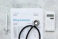 Health care billing statement with doctor`s stethoscope and pen on stone background top view Royalty Free Stock Photo