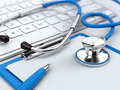 Health care concept - stethoscope on laptop keyboard with clipboard and pen Royalty Free Stock Photo