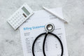 health care costs with billing statement, stethoscope and calculator on stone table top view Royalty Free Stock Photo