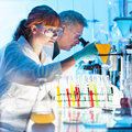 Health care professionals working in laboratory attractive young female scientist and her senior male supervisor pipetting and Royalty Free Stock Images