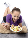 Health conscious young woman beautiful attractive happy smiling vegetarian eating healthy fresh organic salad from a plate lie Stock Photos