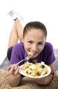 Health conscious young woman beautiful attractive happy smiling vegetarian eating healthy fresh organic salad from a plate lie Royalty Free Stock Image