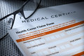 Health cover claim form a with reading glasses Stock Photography