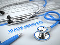 Health insurance concept - stethoscope on laptop keyboard with clipboard and pen Royalty Free Stock Photo