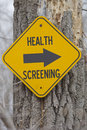 Health screening this way a yellow sign on a tree showing which for making a great employer insurance concept Stock Photography