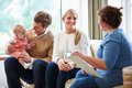 Health visitor talking to family with young baby female Royalty Free Stock Photos