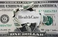 Healthcare costs hole torn in a dollar bill with text Stock Photo