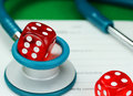 Healthcare gamble a doctors light blue colored stethoscope with a red dice resting on the top of it both resting on a doctors sick Royalty Free Stock Photo