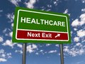 Healthcare next exit green highway sign with text with directional arrow against blue skies with clouds Stock Photos