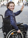 Healthcare wheelchair user a bright smile from a friendly young man sitting in his Royalty Free Stock Image