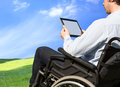 Healthcare wheelchair user disabled young men looking at digital tablet outdoors with blue sky Stock Images
