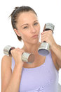 Healthy aggressive fit determined young woman training with dumb bell weights a dslr royalty free image a holding two or in both Royalty Free Stock Photos