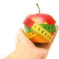 Healthy apple hand holding an wrapped in measuring tape isolated on white Stock Photo
