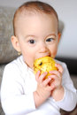 Healthy baby girl having an apple bite expressive with a big yellow in hands a off it on the bed Stock Photos