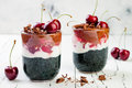 Healthy Black Forest dessert. Black activated charcoal chia pudding with cherries, coconut cream and chocolate. Vegan breakfast Royalty Free Stock Photo