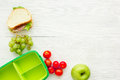 Healthy break with apple, grape and sandwich in lunchbox on home table flat lay mock-up Royalty Free Stock Photo