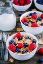 A healthy breakfast bowl. Whole grain cereal with fresh blueberries and raspberries on wooden background. Royalty Free Stock Photo