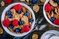 A healthy breakfast bowl. Whole grain cereal with fresh blueberries and raspberries on wooden background. Top view Royalty Free Stock Photo