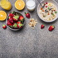 Healthy breakfast cereal with dried fruits, fresh orange juice, a plate of strawberries on wooden rustic background top view borde Royalty Free Stock Photo