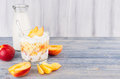 Healthy breakfast with corn flakes, slice peach and milk bottle on white wood board. Decorative border with copy space. Royalty Free Stock Photo