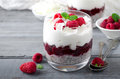 Healthy breakfast, desert, with chia seed pudding, cream, raspberry jam, coconut flakes and fresh berries