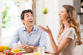 Healthy breakfast with fun surprised man looking at young woman playing fruit in kitchen Royalty Free Stock Photos