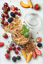 Healthy breakfast ingredients. Oat granola in glass jar with peach, strawberry, sweet cherries, blackberries on light Royalty Free Stock Photo