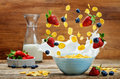 Healthy breakfast with milk, flying corn flakes, strawberries an Royalty Free Stock Photo