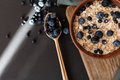 Healthy breakfast. Oat granola with fresh blueberries and currants in a clay bowl over dark grunge surface. Top view Royalty Free Stock Photo