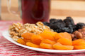 Healthy collection of dried fruits and nuts apricot plums walnuts hazelnuts in a white plate with a drinkn Stock Images