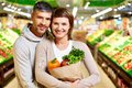 Healthy couple image of happy with paperbag full of products looking at camera in supermarket Stock Photography