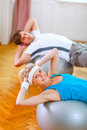 Healthy couple making abdominal crunch on ball Stock Images